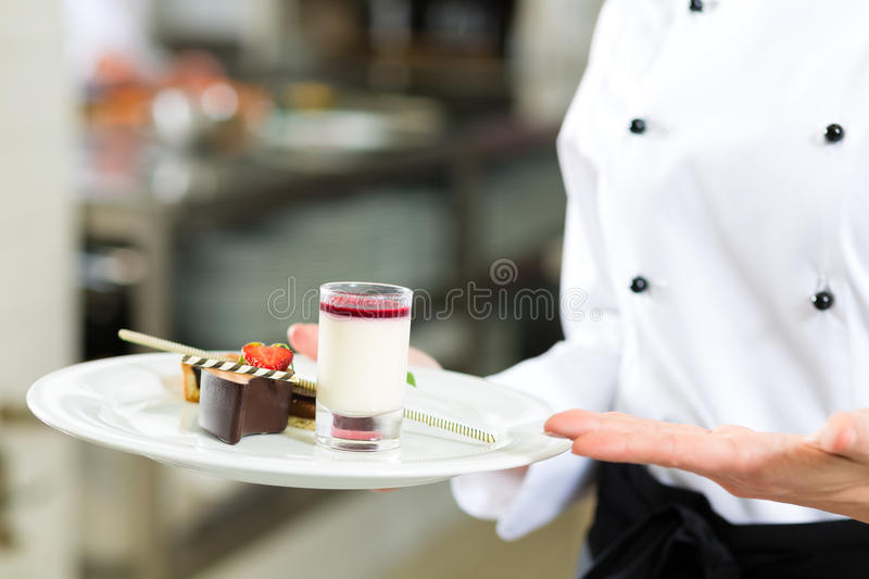 Cook, pastry chef, in hotel or restaurant kitchen. Cook, the female pastry chef, in hotel or restaurant kitchen cooking, she is finishing a sweet dessert stock images