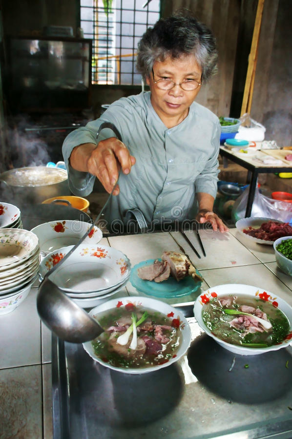 Cook at Pho restaurant. Cook spooning sauce out the bowl that have: noodle, beef, onion to server for customer at Pho restaurant, Daklak, Viet Nam, September 2 stock photos