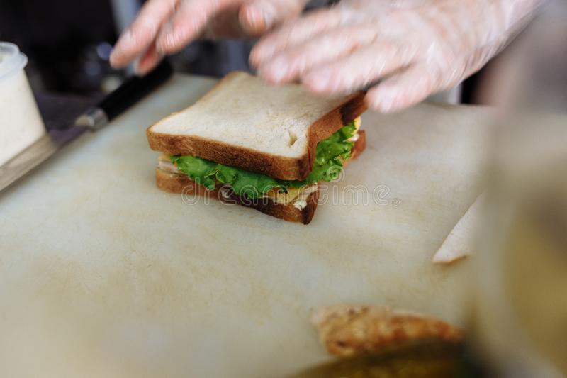 Cook in polyethylene gloves making a sandwich on a white board royalty free stock images