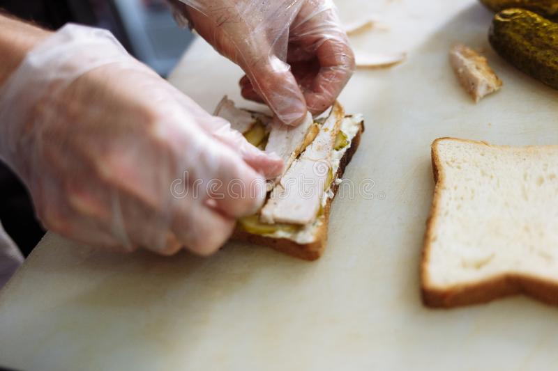 Cook in polyethylene gloves making a sandwich on a white board stock photography