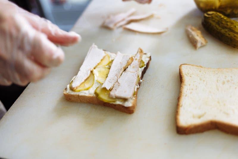 Cook in polyethylene gloves making a sandwich on a white board. Cook in plastic gloves making a sandwich on a white board royalty free stock photos