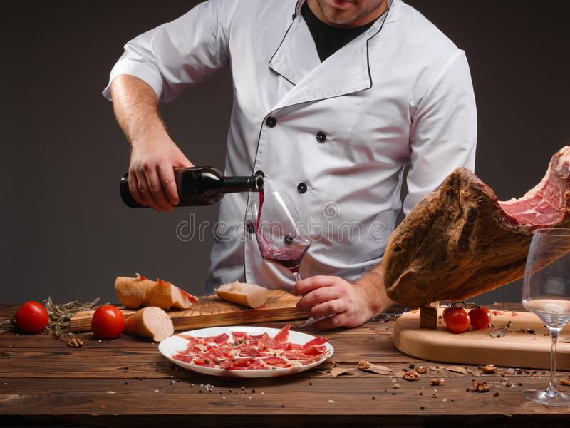 The cook pours the wine into a glass. A bottle of wine, spices, jamon, tomatoes, a wooden table. Closeup image royalty free stock images
