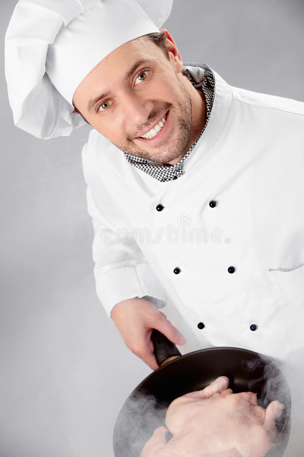 The cook prepares. A hen in a frying pan royalty free stock image