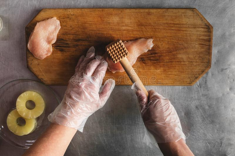 Cook prepares chicken on a wooden cutting board, hands, chicken, pineapple, gloves. meat tenderizer. recipe for chicken royalty free stock photos