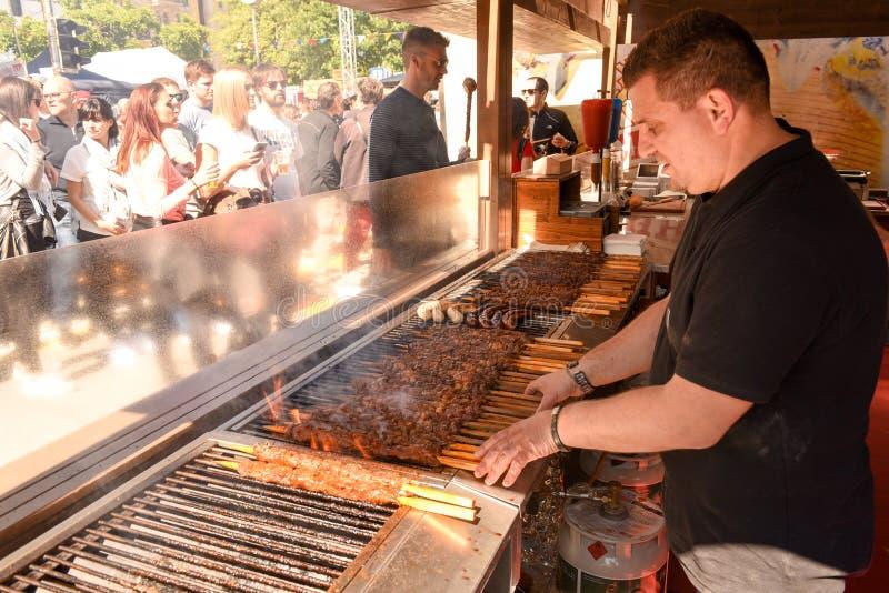 Cook preparing grilled meat skewers at street food festival stock images