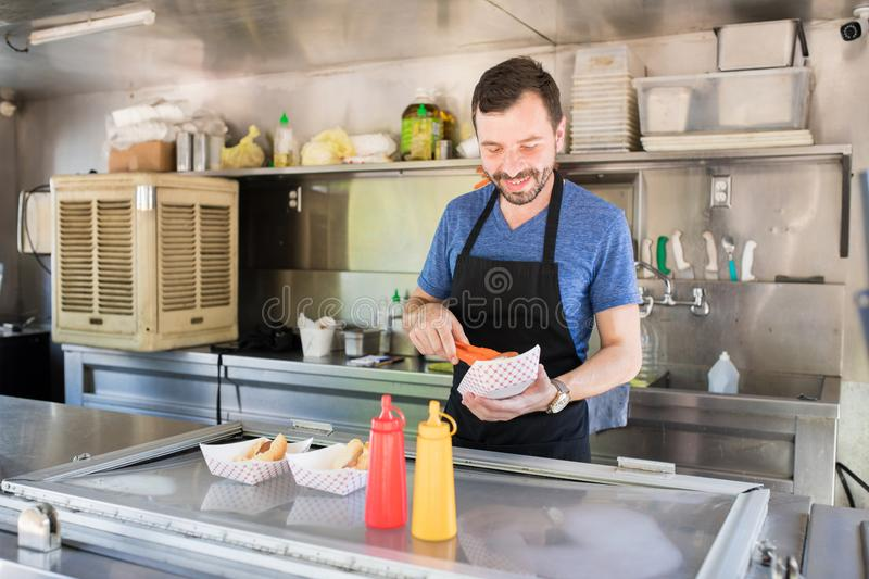 Cook preparing hot dogs stock image