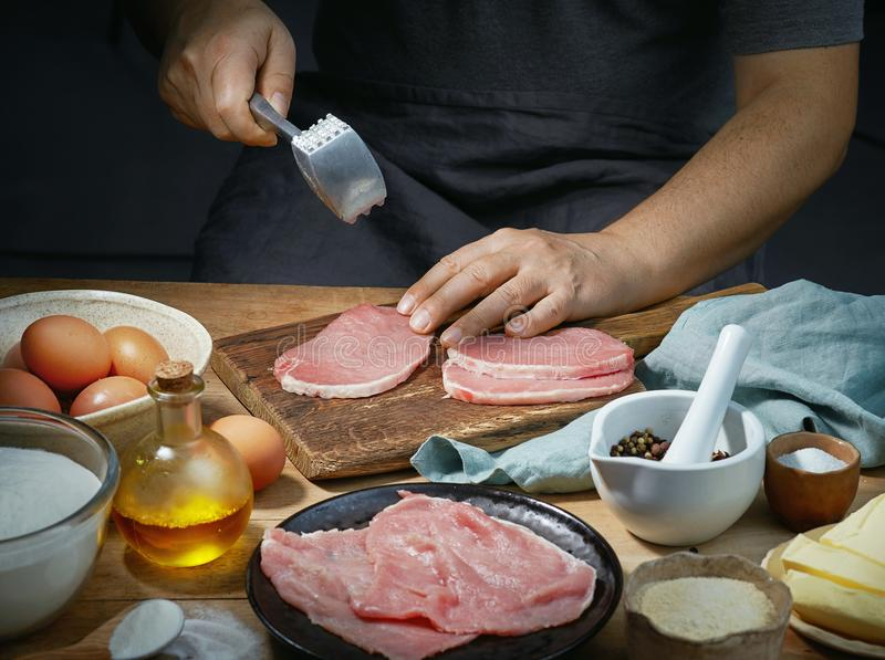 Cook is preparing meat. For making schnitzel stock photo