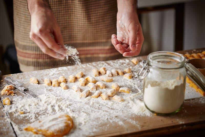 Cook preparing raw pumpking gnocchi stock images
