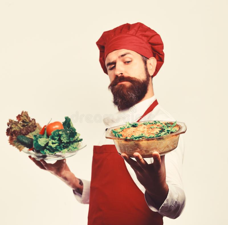 Cook with proud face in burgundy uniform holds baked dish. And salad. Chef holds bowl with potato casserole and vegetables. Man with beard on white background stock photo
