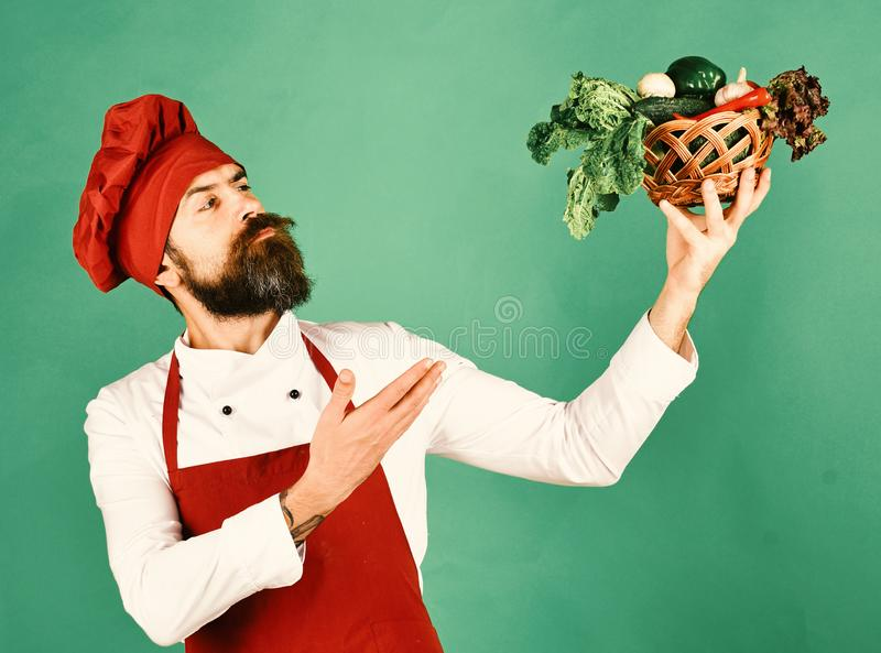 Cook with proud face in burgundy uniform presents vegetables. In wicker bowl. Chef holds lettuce, tomato, pepper and mushrooms. Vegetarian restaurant concept stock photos