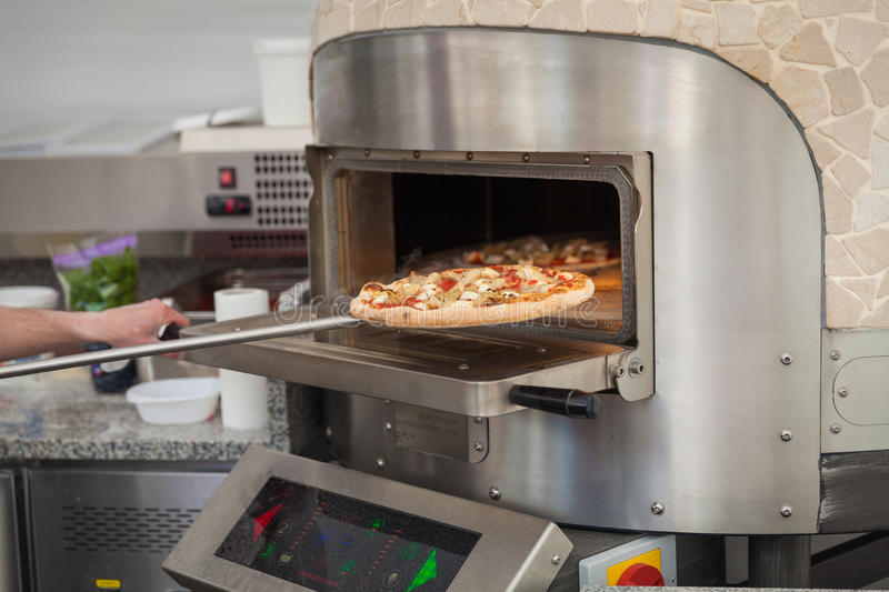 Cook pulls lave baked pizzas. From a stone oven royalty free stock photo