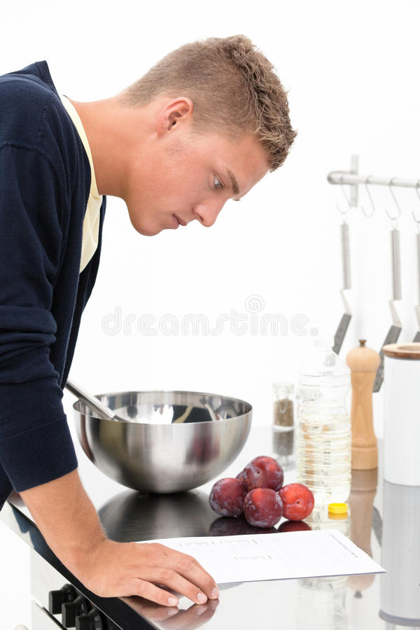 Cook with recipe. Young handsome blond man standing in the kitchen and reading recipe stock photography