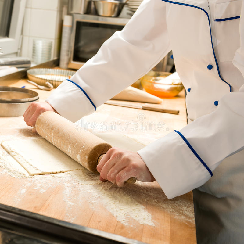 Cook rolling dough kitchen with rolling pin. Cook rolling dough in kitchen with rolling pin and flour stock images