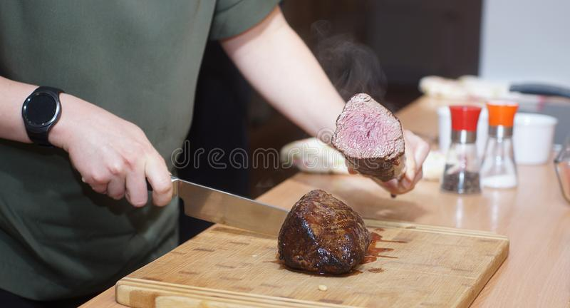 A cook with a round clock cuts a beef tenderloin and checks the readiness royalty free stock photography