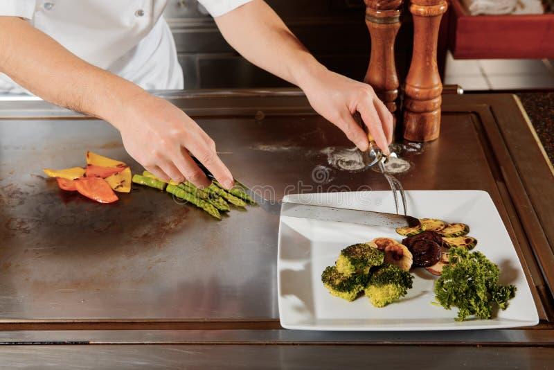 Cook słuzyć posiłek na talerzu obraz stock