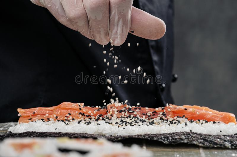 Cook`s hands close-up. A male chef makes sushi and rolls from rice, red fish and avocado. White gloves. royalty free stock photos