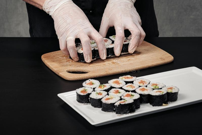 Cook`s hands close-up. A male chef makes sushi and rolls from rice, red fish and avocado. White gloves. stock images