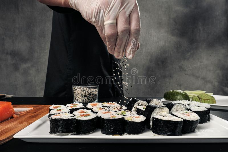 Cook`s hands close-up. A male chef makes sushi and rolls from rice, red fish and avocado. White gloves. royalty free stock image