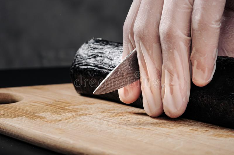 Cook`s hands close-up. A male chef makes sushi and rolls from rice, red fish and avocado. White gloves. stock image