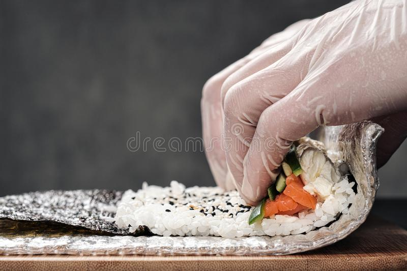 Cook`s hands close-up. A male chef makes sushi and rolls from rice, red fish and avocado. White gloves. stock photos