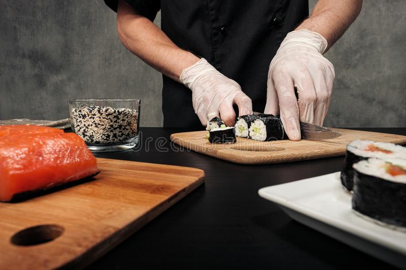 Cook`s hands close-up. A male chef makes sushi and rolls from rice, red fish and avocado. White gloves. royalty free stock photography