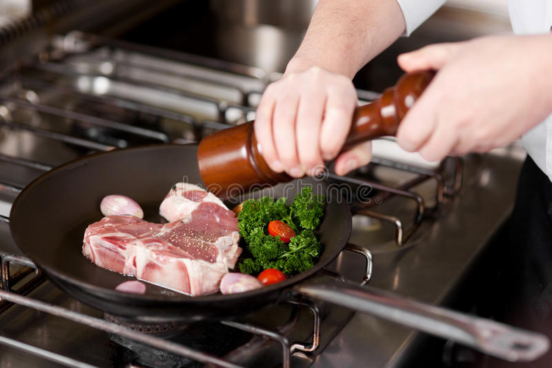 Cook seasoning meat with pepper. From a pepper mill stock photos