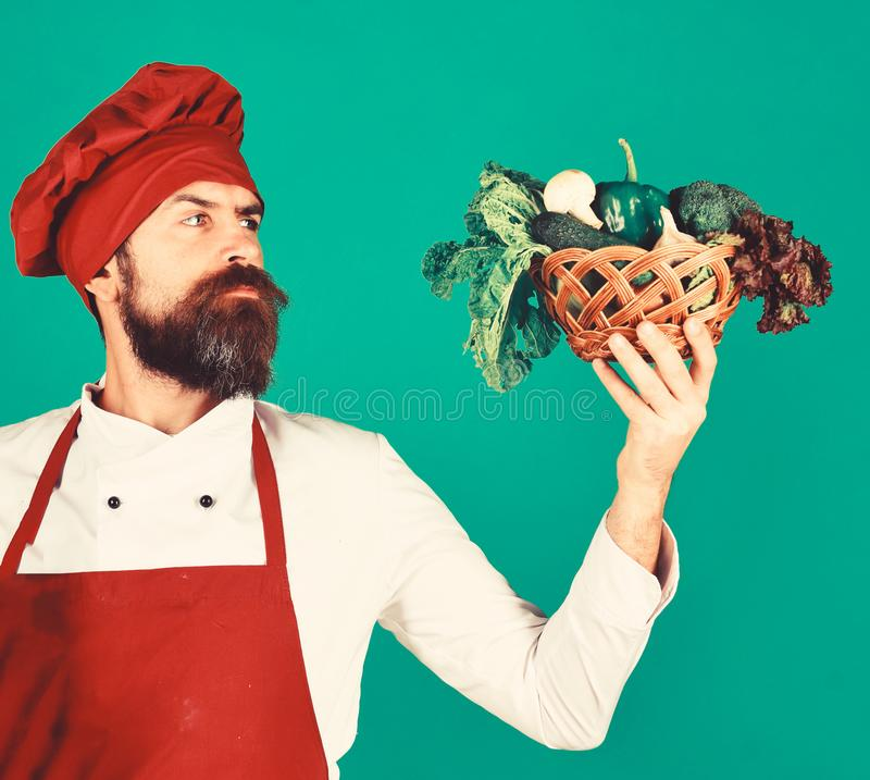 Cook with serious face in burgundy uniform looks at vegetables. In wicker bowl. Healthy cooking concept. Man with beard on green background. Chef holds broccoli stock photography