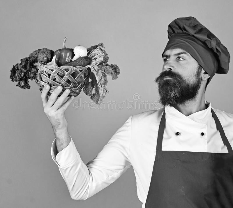 Cook with serious face in burgundy uniform looks at vegetables. In wicker bowl. Healthy cooking concept. Man with beard on green background. Chef holds broccoli stock photos