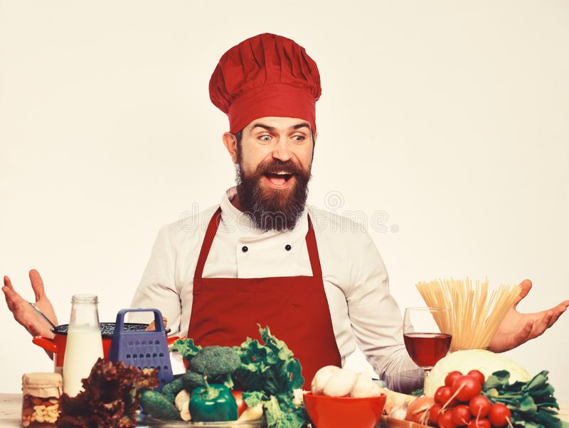 Cook with shocked face in burgundy uniform sits by table. With vegetables and kitchenware. Professional cookery concept. Chef prepares meal. Man with beard royalty free stock images