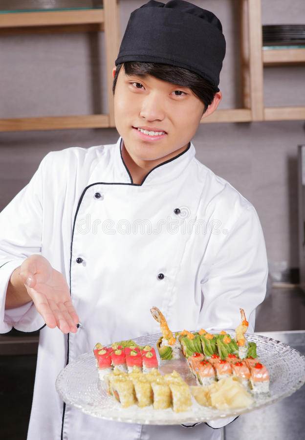 Cook shows a sushi set. Proud cook. Confident young Asian sushi cook points with hand on a plate with sushi set royalty free stock photos