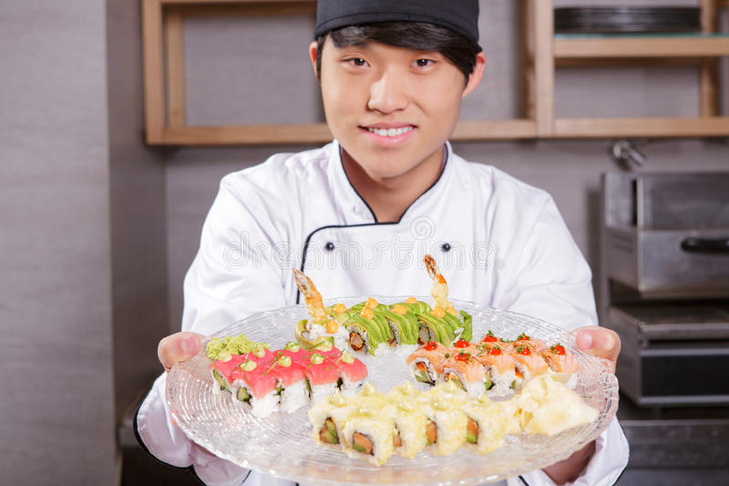 Cook shows a sushi set. Tasty meal for big company. Young and smiling Asian cook in white uniform stretching out a big plate with various kinds of sushi rolls on stock photography