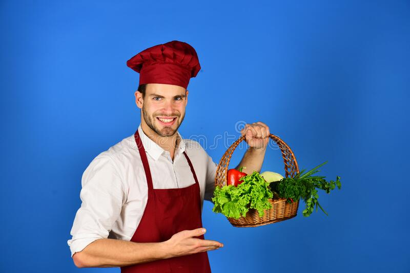 Cook with smiling face holds wicker basket of fresh veggies. stock photo