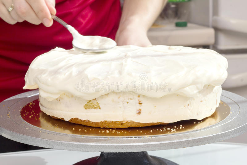 Cook spreads cream on the cake. Cook spreads white cream on the cake stock image