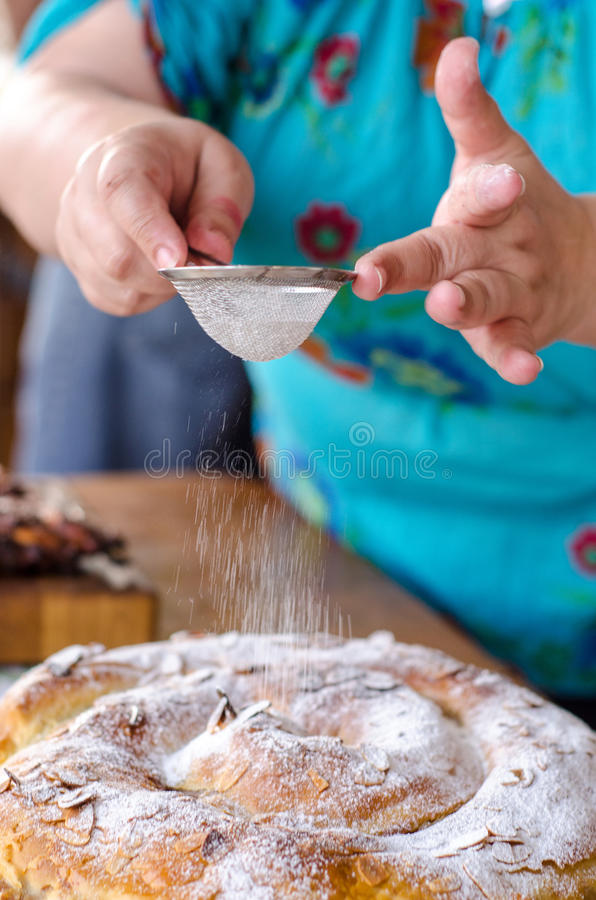 Cook sprinkles sugar on cake royalty free stock photography