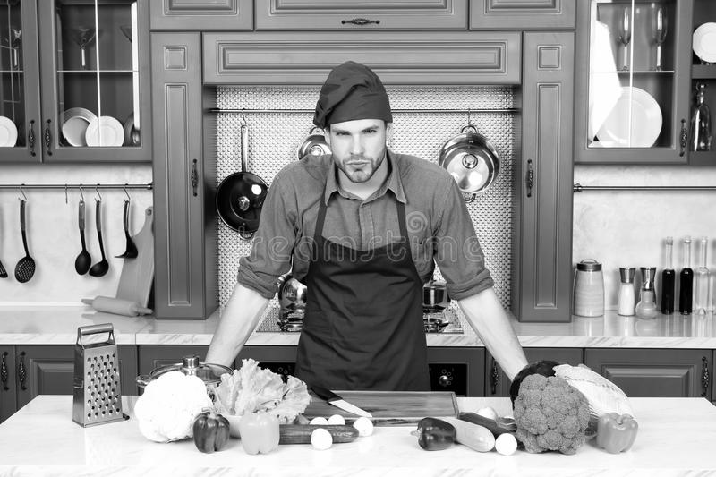 Cook stand at kitchen table. Man in chef hat and apron in kitchen. Vegetables and tools ready for cooking dishes stock photos