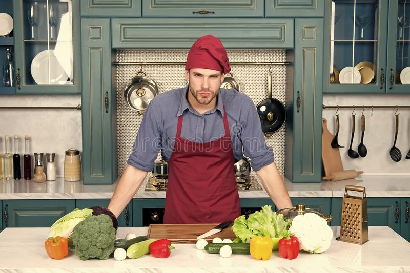 Cook stand at kitchen table. Man in chef hat and apron in kitchen. Vegetables and tools ready for cooking dishes royalty free stock images