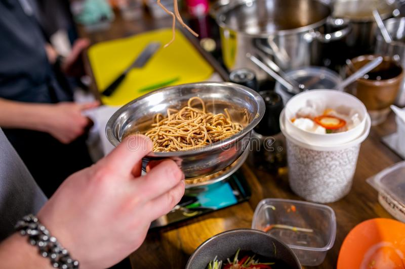 Cook takes boiled noodles in a colander. Master class in the kitchen. The process of cooking. Step by step. Tutorial. Close-up royalty free stock photography