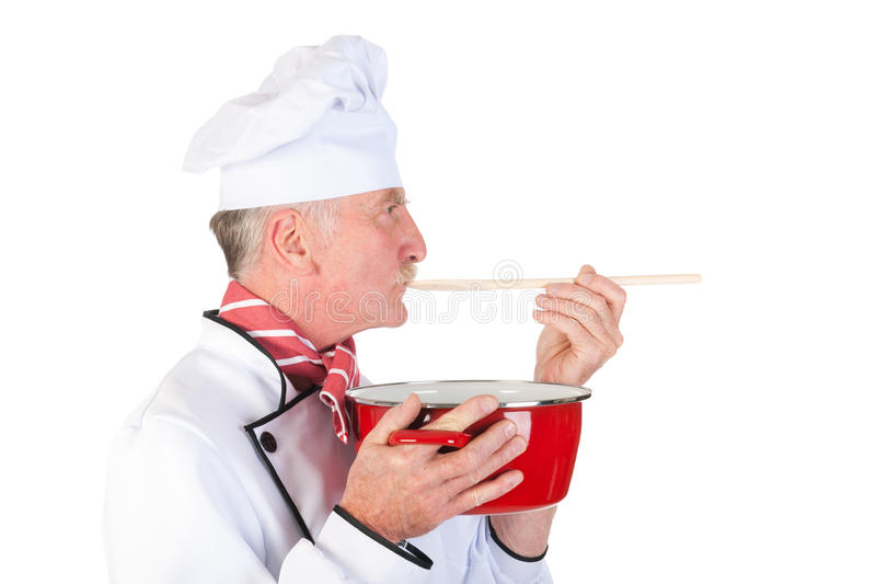 Cook taste the food. Cook is tasting the food with wooden spoon and red pan stock photos