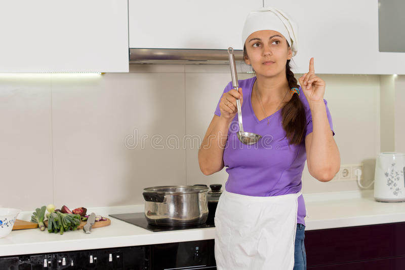 Cook tasting her food thinking what is missing stock photography
