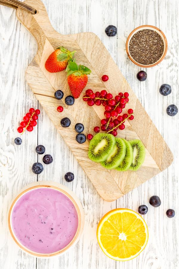 Cook trendy breakfast. Acai smoothie bowl near cutting board with fresh fruits, berries, chia seeds on white wooden royalty free stock images