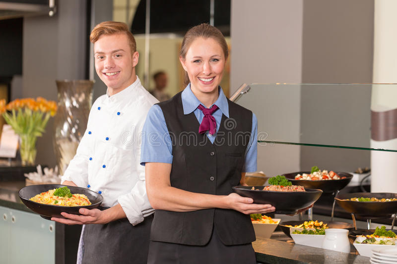 cook and waitress from catering service posing in front of buffet stock photos