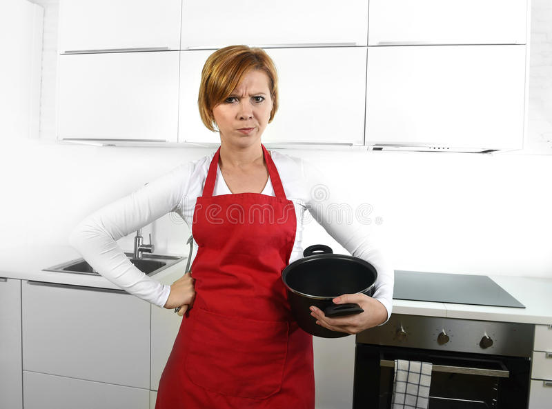 Cook woman in angry upset frustrated face expression in apron holding cooking pan dirty edit royalty free stock images