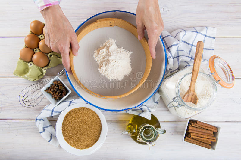 Cook woman sieving flour with her hands stock images
