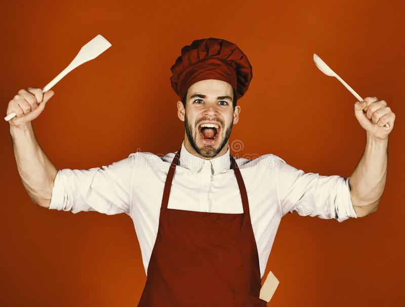 Cook works in kitchen. Chef with excited face holds wooden spoon and spatula on red background. Kitchenware and cooking stock image