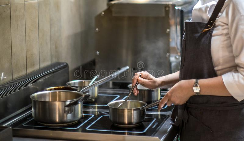 Cook works in the kitchen. Cooking food. Restaurant, chef. royalty free stock photos