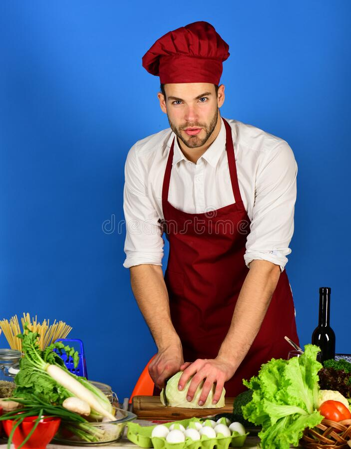 Cook works in kitchen near table with vegetables and tools. royalty free stock photography