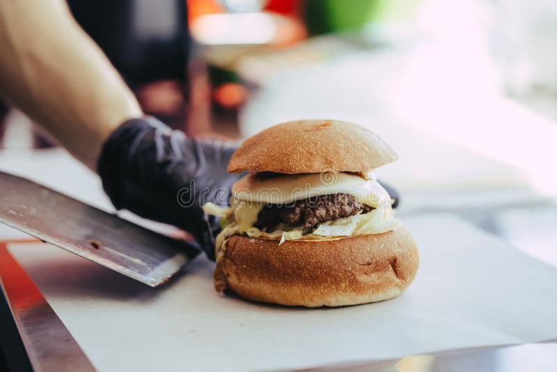 Cook wr?cza narz?dzanie i robi? hamburger obraz royalty free