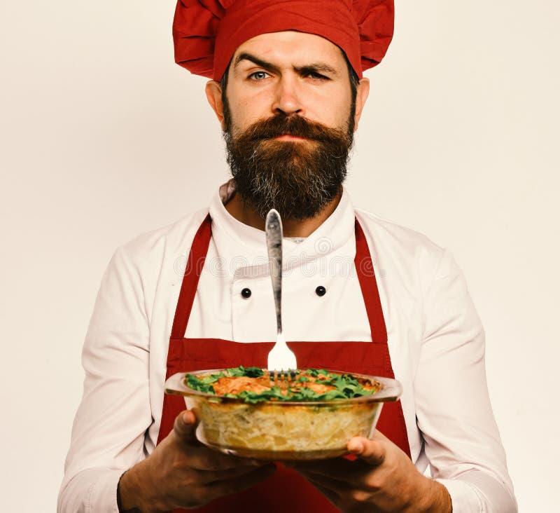 Cook z ufną twarzą w Burgundy munduru chwyt piec naczyniu Mężczyzna z brodą na białym tle gotować i obraz stock