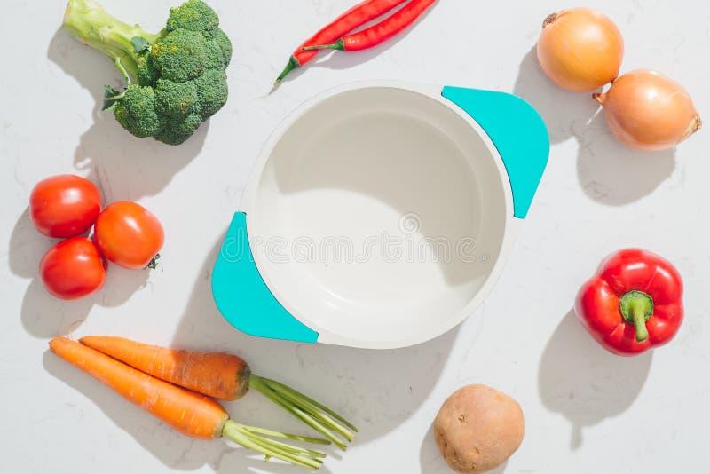 Cookbook. Fresh vegetables around white pot. Top view. royalty free stock photos