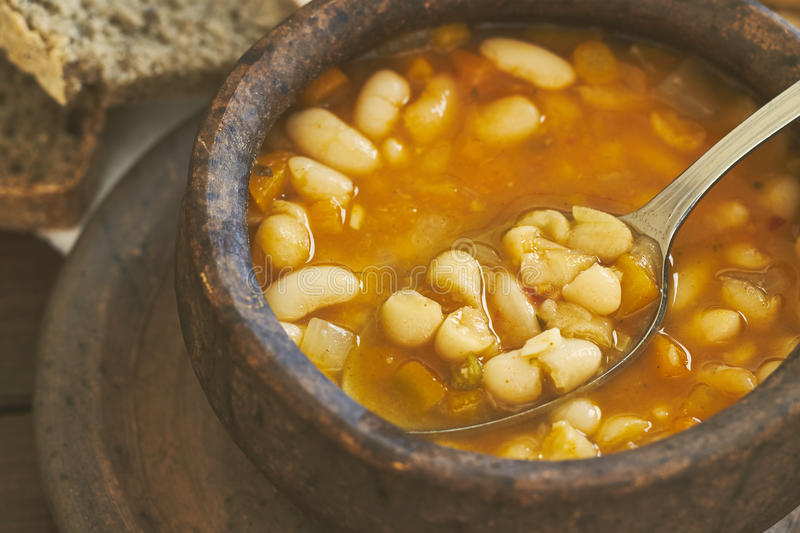 Cooked beans in clay bowl. Closeup of cooked beans in clay bowl with spoon and whole wheat bread in background royalty free stock photos